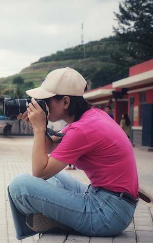 photo person women holding a camera while sitting during daytime apparel free for commercial use images