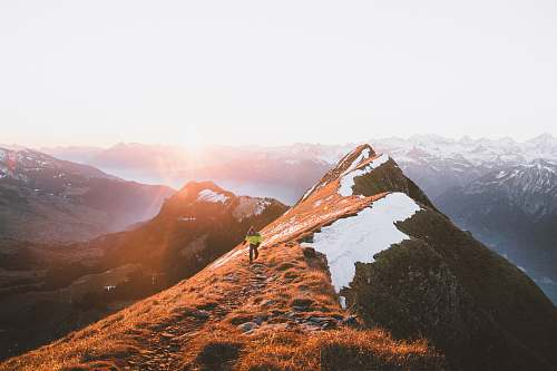 nature A person walking on a rocky path along the mountain ridge outdoors