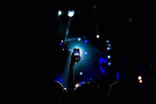 photo phone low light photography of person raising hand holding smartphone light free for commercial use images