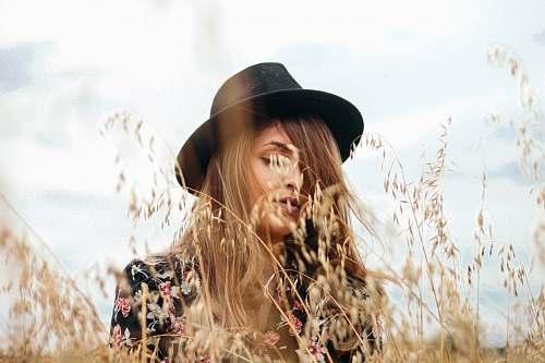 woman woman wearing black hat near brown grass during daytime girl