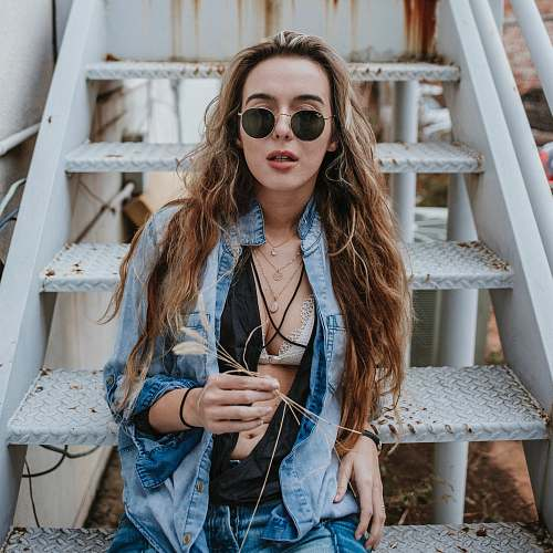 denim woman wearing black sunglasses on stairs woman