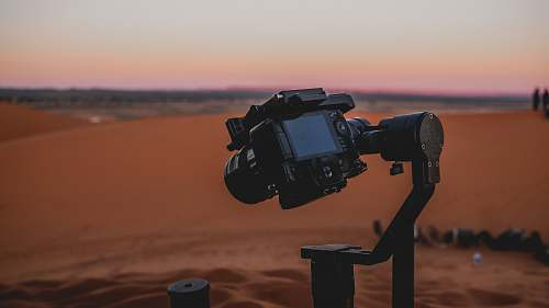 photo human black DSLR camera mounted on stabilizer at the desert soil free for commercial use images