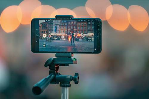 photo bokeh photography of a smartphone showing picture of the city street tripod