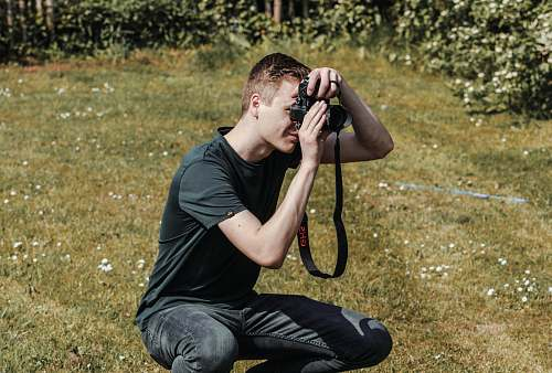 photo human man holding black DSLR camera photographer free for commercial use images