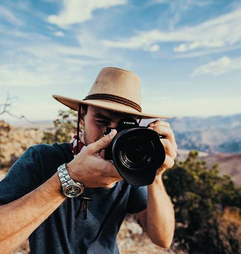 photo human man holding DSLR camera camera free for commercial use images