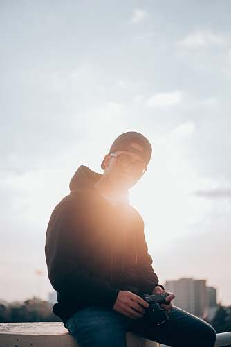 photo human man in black hoodie sitting on railings holding camera flare free for commercial use images