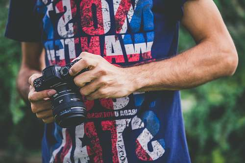 photo people man in blue shirt holding DSLR camera camera free for commercial use images