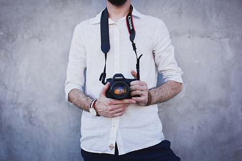 human man in white dress shirt holding Canon DSLR camera lens