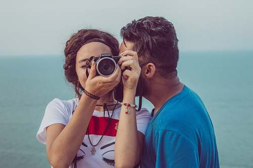 human man kissing woman's cheek while taking photo tunisie