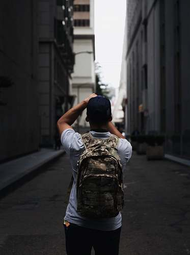 backpack man standing between two buildings urban