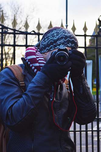 photo photographer man wearing black jacket using black Canon DSLR camera near black metal gate apparel free for commercial use images
