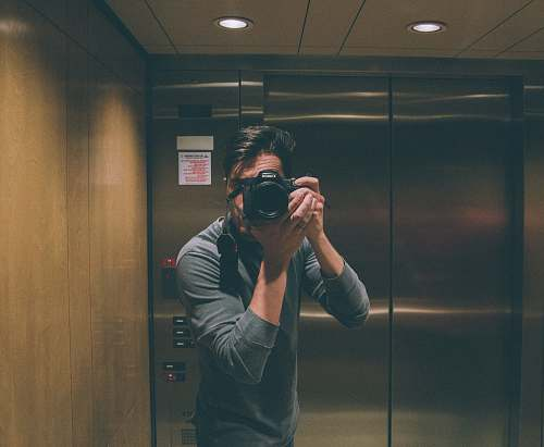 photo human person holding DSLR camera elevator free for commercial use images