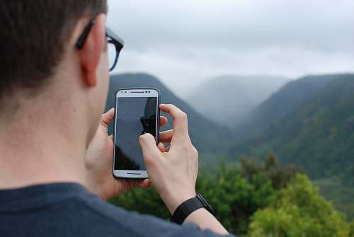 phone person taking photo of hills during daytime cell phone