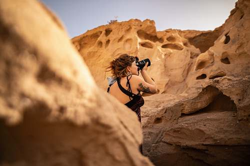 human photography of woman standing near rock formation while taking photo during daytime nature