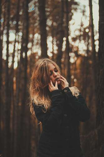 people portrait photography of woman wearing black coat surrounded by forest trees during daytime female