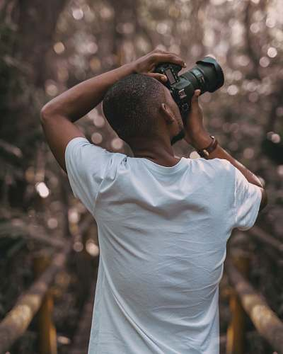 photo human selective focus photography of a man in white t-shirt using a DSLR camera photographer free for commercial use images