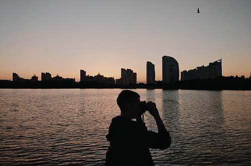 photo human silhouette of person using binoculars photographer free for commercial use images