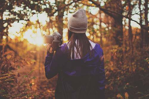 girl woman in forest holding DSLR camera during golden hour human