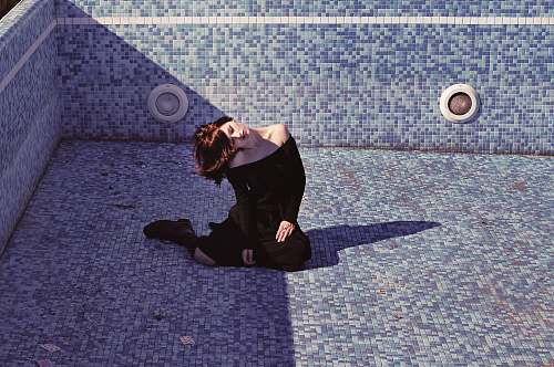 human woman sitting inside the empty pool black