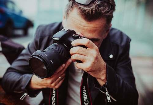 man man holding up Canon DSLR camera male