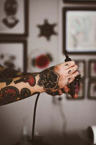 hands shallow focus photography of person holding black tattoo machine ornament