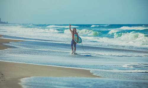 water man carrying surfboard at beach ocean
