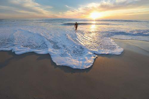 ocean man standing on seashore during sunset water