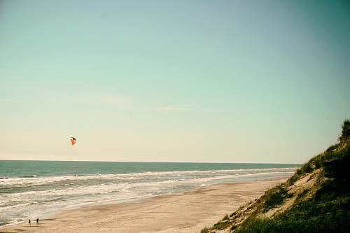 water person flying kite on seashore ocean