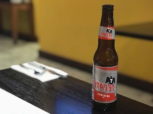 alcohol Tecate beer bottle on coffee table beverage