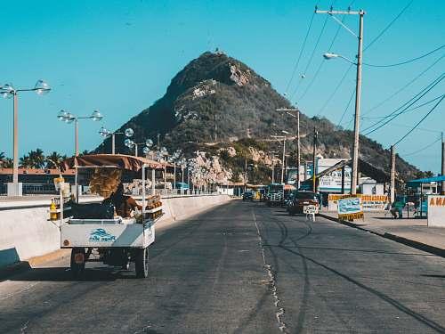mazatlan white auto rickshaw on riding on asphalt road towards green mountain road