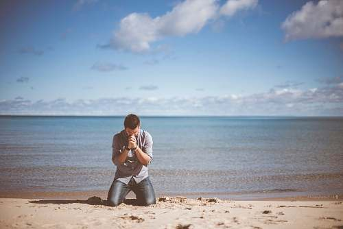 person man kneeling down near shore beach