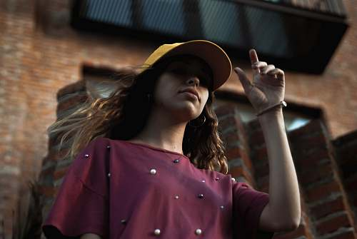 human low angle of woman standing near brick building hat