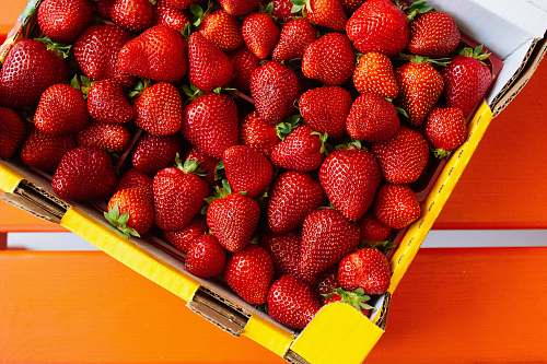 fruit red strawberries on yellow plastic container plant