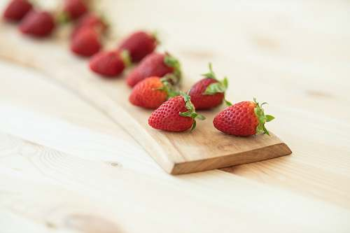 food red strawberries on brown wooden chopping board strawberry
