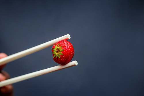 food red strawberry fruit on white stick plant
