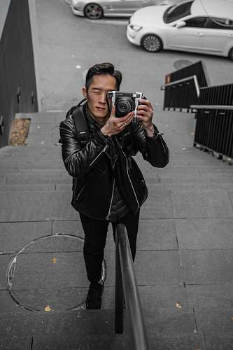 clothing shallow focus photo of man in black leather jacket using camera coat