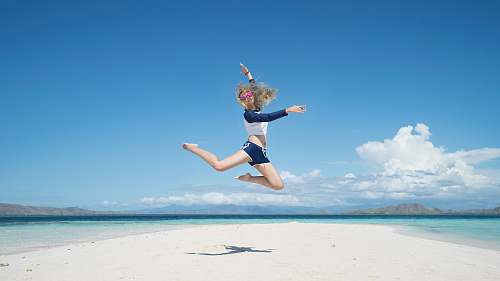 photo sea woman jumping with raising her right hand sand free for commercial use images
