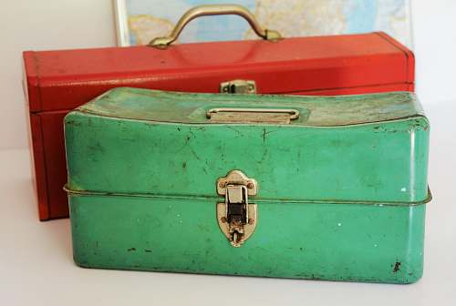 toolbox two rectangular green and red tool cases on white surface metal worker
