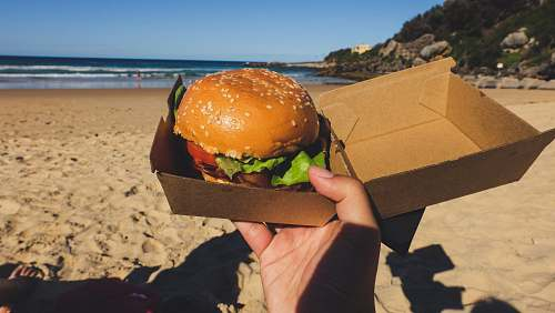 food person holding box with burger and lettuce sandwich