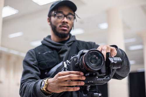 photo human man using black Canon DSLR camera person free for commercial use images