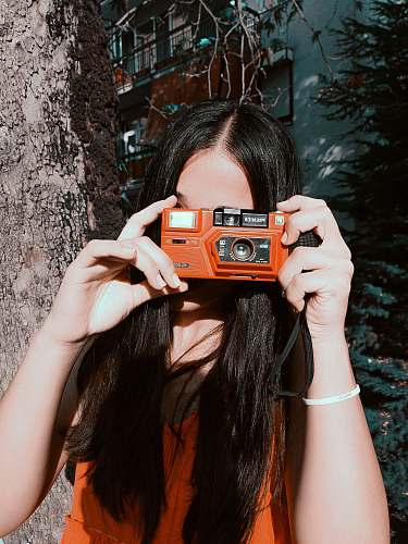 photo person woman holding orange camera human free for commercial use images