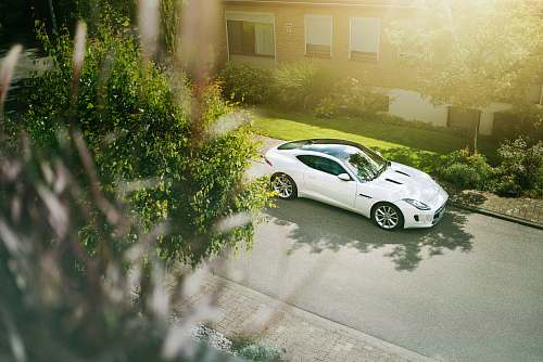 automobile white coupe parked near house sports car