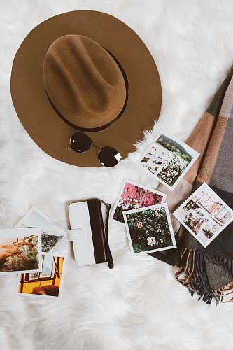 photo art gold-colored framed sunglasses on brown hat beside white and black leather wristlet surrounded by photos on white and gray floral textile hipster free for commercial use images