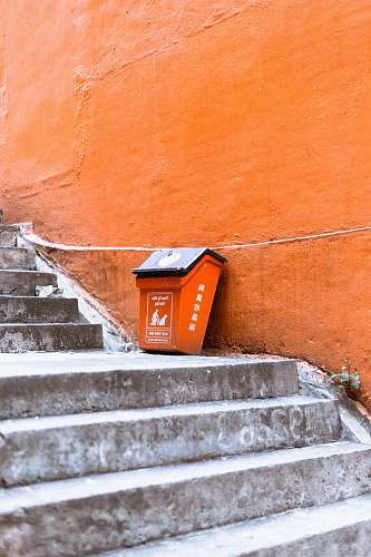 banister orange and black plastic trash bin beside orange painted wall staircase