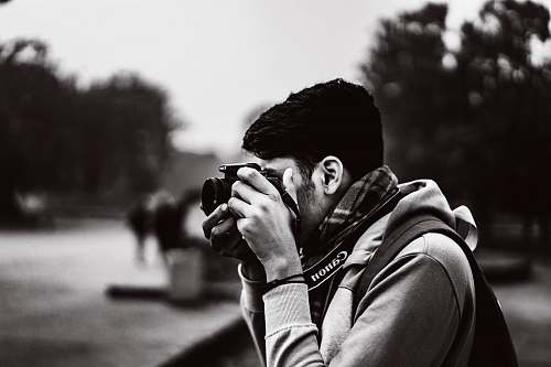 person grayscale photography of man taking photo using camera camera