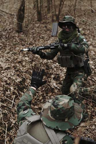 military man holding assault rifle in the middle of forest military uniform