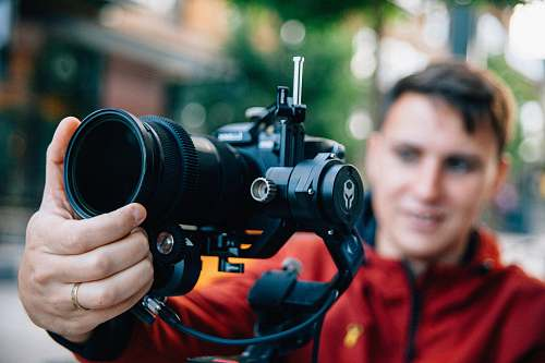 person man holding black Canon DSLR camera \during daytime camera