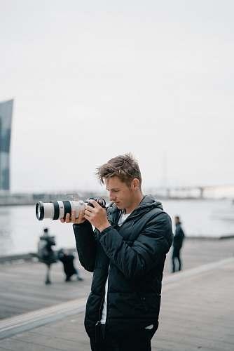 person man holding black DSLR camera outdoors photographer