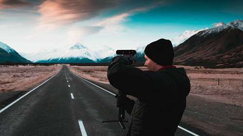 person man holding camera while standing on paved road road