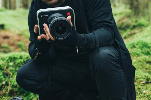 photo electronics man in black jacket holding DSLR camera camera free for commercial use images